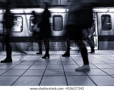 People getting off the subway train. Motion blur. City life. Toned image. Cold tone. - stock photo