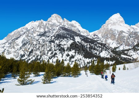 People go snowshoeing on the trail up the hill. Wyoming, Grand Teton National Park - stock photo