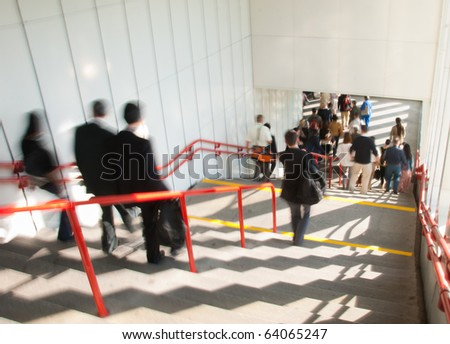 People go through an underpass. Blurred motion. - stock photo