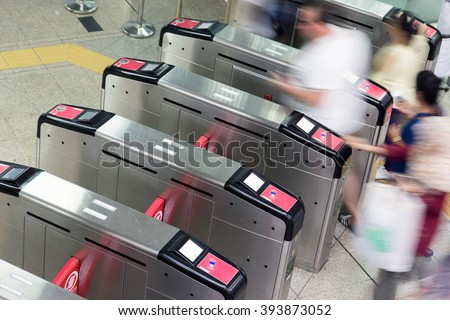 People going through the turnstile in the subway. Passengers in the subway. Tourists walk in the turnstile railway station. Metro station turnstiles. Entrance to the metro station turnstiles. - stock photo