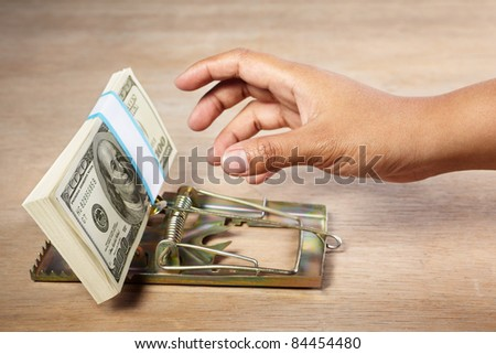 People hand is about to catch the money placed on mousetrap