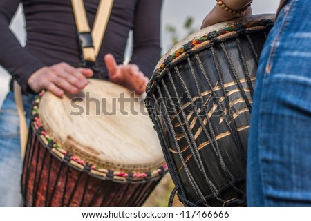 People hands playing music at djembe drums - stock photo