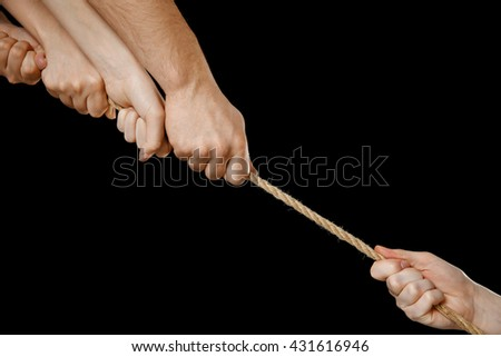 People hands pulling the rope on black background - stock photo