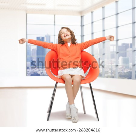 people, happiness, childhood and furniture concept - happy little girl sitting on chair with spreaded arms over empty living room background - stock photo