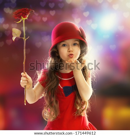 People, happiness concept. Happy little girl with rose in red clothes sends kiss her hand - stock photo