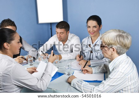 People having a meeting conversation and they sitting around a table on blue background - stock photo