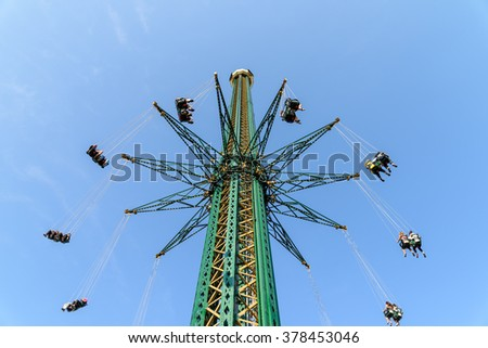 People Having Fun In Carousel Swing Ride At Amusement Park - stock photo