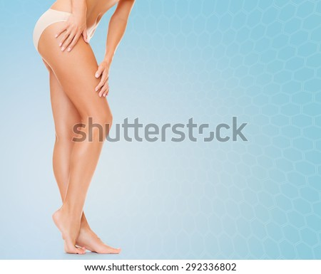 people, health and beauty concept - woman with long legs in cotton panties touching her hips over blue background - stock photo