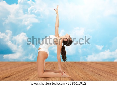 people, health and wellness concept - woman in cotton underwear doing yoga exercise on wooden floor over white clouds and blue sky background - stock photo