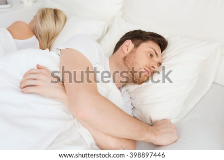 people, health, sleep disorder concept - couple lying back to back in bed at home and young man suffering from insomnia - stock photo