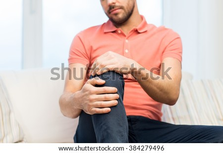 people, healthcare and problem concept - close up of young man suffering from pain in leg or knee at home - stock photo