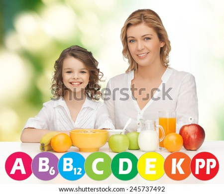 people, healthy lifestyle, family and food concept - happy mother and daughter eating healthy breakfast over green background with vitamins - stock photo