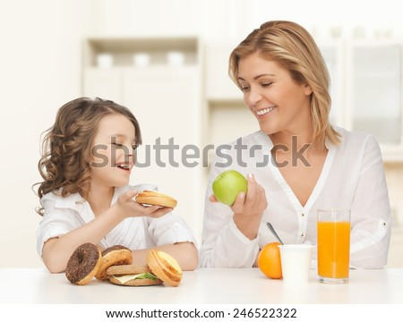 people, healthy lifestyle, family and food concept - happy mother and daughter eating healthy breakfast over home kitchen background - stock photo