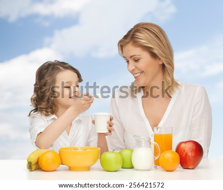 people, healthy lifestyle, family and food concept - happy mother and daughter eating healthy breakfast over blue sky background - stock photo