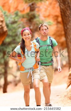 People hiking - couple hikers in Bryce Canyon walking smiling happy together. Multiracial couple, young Asian woman and Caucasian man in Bryce Canyon National Park landscape, Utah, United States. - stock photo