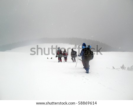 People hiking up the mountain covered in heavy snow