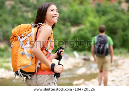 People hiking - woman hiker walking in Zion National Park, man in background. Hikers trekking by river water creek in forest enjoying view smiling happy. Young couple on trek hike in Utah, USA. - stock photo