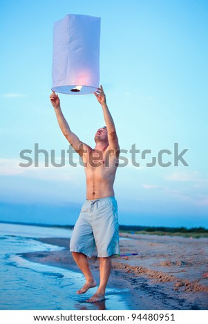 People holding a flying fire lantern - stock photo
