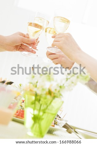 People holding glasses of white wine - stock photo