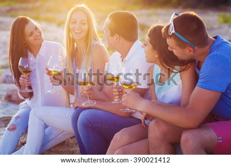 People holding glasses of white wine and talking at the beach picnic - stock photo