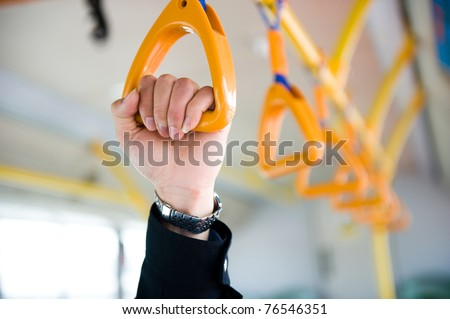 people holding onto a handle on a train. - stock photo