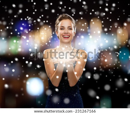 people, holidays, advertisement, christmas and luxury concept - laughing woman in evening dress holding something imaginary over night lights and snow background - stock photo