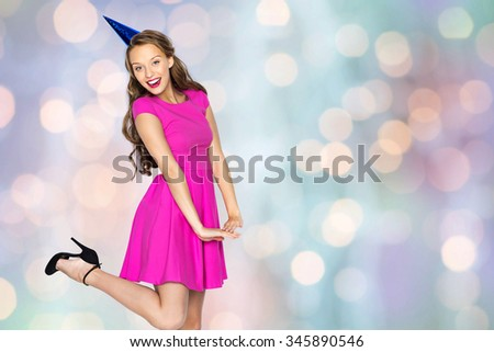 people, holidays and celebration concept - happy young woman or teen girl in pink dress and party cap over holidays lights background - stock photo
