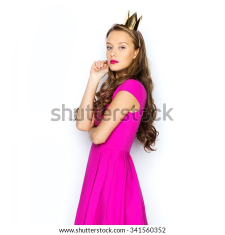 people, holidays and fashion concept - young woman or teen girl in pink dress and princess crown - stock photo