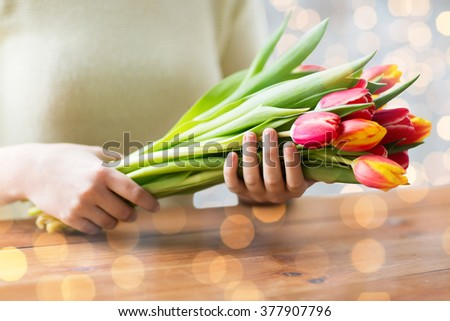 people, holidays and gardening concept - close up of woman holding tulip flowers - stock photo