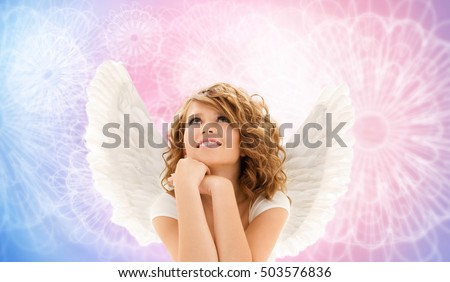 people, holidays and religious concept - happy young woman or teen girl with angel wings over rose quartz and serenity pattern background
