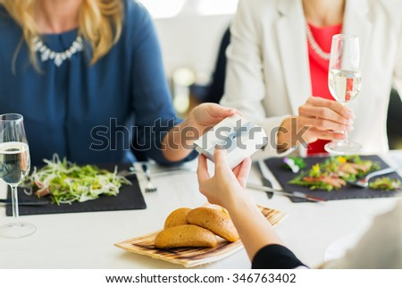 people, holidays, celebration and lifestyle concept - close up of women giving birthday present at restaurant