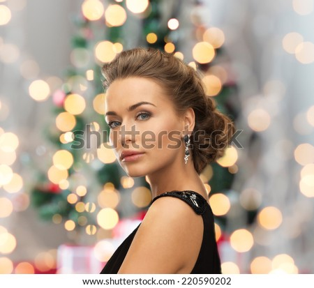 people, holidays, christmas and glamour concept - beautiful woman in evening dress wearing earrings over christmas tree and lights background - stock photo