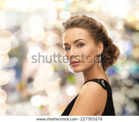 people, holidays, christmas and glamour concept - beautiful woman in evening dress wearing earrings over lights background - stock photo