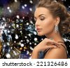 people, holidays, christmas and glamour concept - beautiful woman in evening dress wearing ring and earrings over snowy night city background - stock photo
