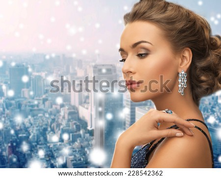people, holidays, christmas and glamour concept - beautiful woman in evening dress wearing ring and earrings over snowy city background - stock photo