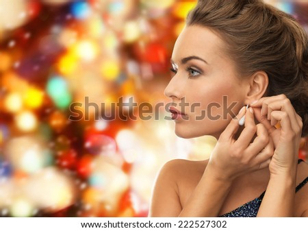people, holidays, christmas and glamour concept - close up of beautiful woman wearing earrings over red lights background - stock photo