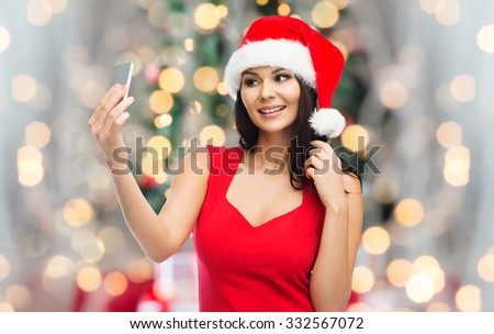 people, holidays, christmas and technology concept - beautiful sexy woman in red santa hat taking selfie picture by smartphone over christmas tree lights and presents background - stock photo