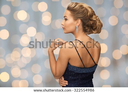 people, holidays, christmas, jewelry and glamour concept - beautiful woman with diamond earring over lights background - stock photo