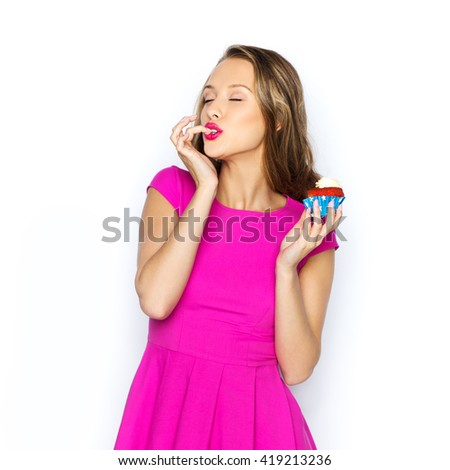 people, holidays, party, junk food and celebration concept - happy young woman in pink dress eating birthday cupcake - stock photo