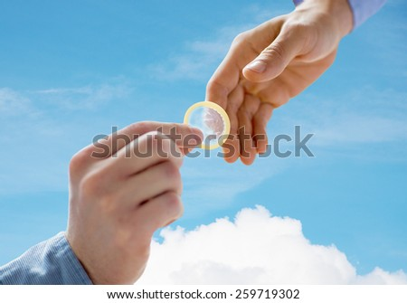 people, homosexuality, safe sex, sexual education and charity concept - close up of happy male gay couple hands giving condom over blue sky and cloud background - stock photo