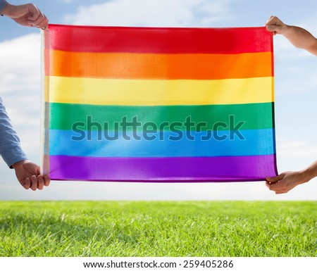 people, homosexuality, same-sex, gay and love concept - close up of happy male gay couple hugging and holding rainbow flag over blue sky and grass background - stock photo