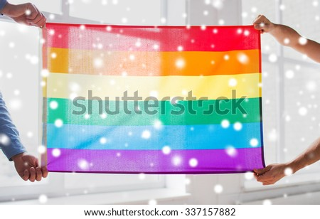 people, homosexuality, same-sex, gay and love concept - close up of happy male gay couple hugging and holding rainbow flag at home over snow effect - stock photo