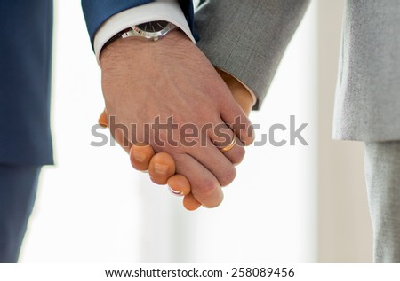 people, homosexuality, same-sex marriage and love concept - close up of happy male gay couple holding hands with wedding rings on - stock photo