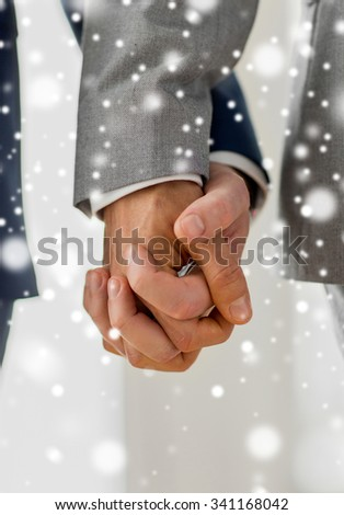 people, homosexuality, same-sex marriage and love concept - close up of happy male gay couple holding hands over snow effect - stock photo