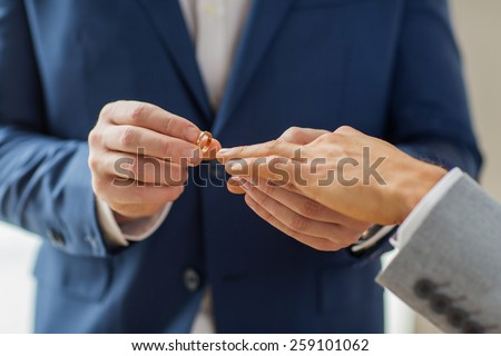people, homosexuality, same-sex marriage and love concept - close up of happy male gay couple hands putting wedding ring on - stock photo