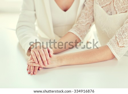 people, homosexuality, same-sex marriage and love concept - close up of happy married lesbian couple hands - stock photo