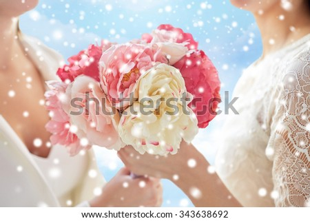 people, homosexuality, same-sex marriage and love concept - close up of happy married lesbian couple with flower bunch blue sky background over snow effect - stock photo