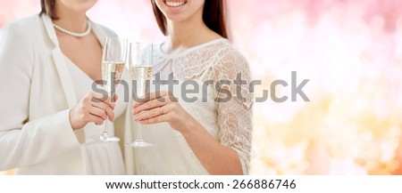 people, homosexuality, same-sex marriage, celebration and love concept - close up of happy married lesbian couple holding and clinking champagne glasses over pink holidays lights background - stock photo