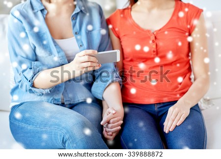 people, homosexuality, same-sex marriage, gay and love concept - close up of happy lesbian couple with smartphone at home over snow effect - stock photo