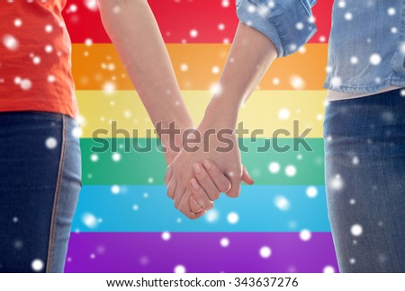 people, homosexuality, same-sex marriage, gay and love concept - close up of happy lesbian couple holding hands over rainbow flag background over snow effect - stock photo